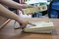 拿着电话接收器和拨号码的女性手 免版税库存照片