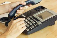 拿着电话接收器和拨号码的女性手 库存照片