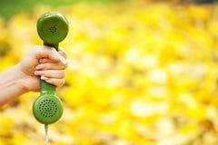 拿着电话接收器的手在秋天公园 库存照片