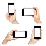 拿着电话用不同的方式的被隔绝的女性手 免版税图库摄影