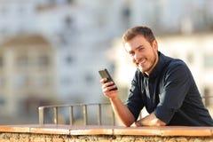 拿着电话的愉快的人看照相机日落 免版税图库摄影