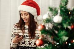 拿着电话的时髦的妇女看屏幕圣诞树 库存图片