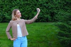 拿着电话的年轻逗人喜爱的女孩在胳膊` s长度和指挥微笑 图库摄影