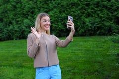 拿着电话的年轻逗人喜爱的女孩在胳膊` s长度和指挥微笑 免版税库存照片