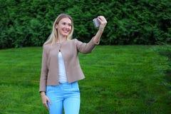 拿着电话的年轻逗人喜爱的女孩在胳膊` s长度和指挥微笑 免版税库存图片