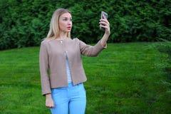 拿着电话的年轻逗人喜爱的女孩在胳膊` s长度和指挥微笑 免版税图库摄影
