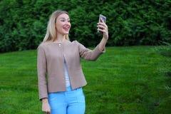 拿着电话的年轻逗人喜爱的女孩在胳膊` s长度和指挥微笑 库存照片