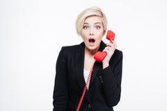 拿着电话管的惊奇女实业家 库存照片