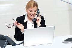 拿着电话联系的妇女的眼睛玻璃 免版税库存照片