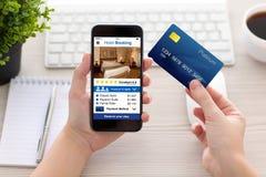 拿着电话app旅馆预定和信用卡的女性手 免版税库存照片