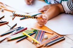 拿着画和绘的亚裔儿童女孩的手蜡笔 图库摄影