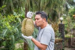 拿着留连果的亚裔农夫是果子的国王 免版税库存照片