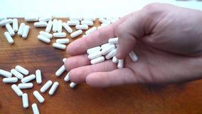 拿着疏散的白色胶囊、药片或者维生素 免版税库存图片