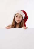 拿着白板和作土佬的圣诞老人帽子的美丽的女孩 图库摄影