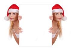拿着白板的圣诞老人帽子的二个女孩 免版税图库摄影