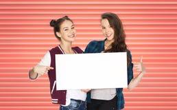 拿着白板的愉快的十几岁的女孩或朋友 免版税库存照片
