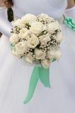 拿着白玫瑰的美丽的花束新娘 免版税库存照片