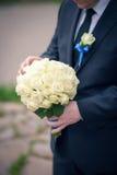 拿着白玫瑰的花束黑经典衣服的人 免版税图库摄影