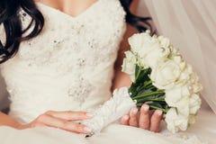 拿着白玫瑰花束的新娘 免版税图库摄影
