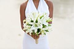 拿着白百合花婚礼花束的新娘 免版税库存图片