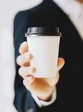 拿着白皮书咖啡杯的商人拿走 嘲笑纸盒咖啡杯为去外面 垂直的大模型 库存照片