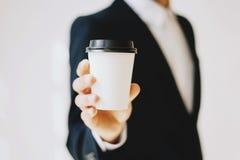 拿着白皮书咖啡杯的商人拿走 嘲笑纸盒咖啡杯为去外面 水平的大模型 库存图片