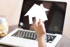 拿着白皮书Origami议院的手 库存图片