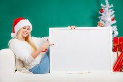 拿着白空白的委员会的圣诞老人帽子的妇女 库存图片