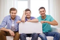 拿着白空白的委员会的微笑的男性朋友 免版税库存照片
