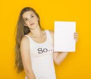 拿着白纸的好年轻可爱的妇女 库存照片