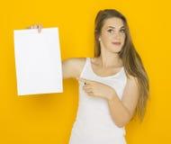 拿着白纸的好年轻可爱的妇女 图库摄影