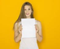 拿着白纸的好年轻可爱的妇女 免版税库存图片
