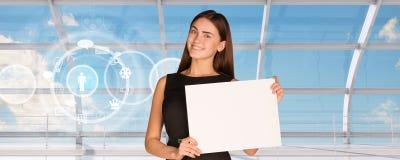 拿着白纸的微笑的年轻女实业家 免版税库存图片