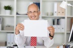 拿着白纸的愉快的商人在书桌 免版税库存图片