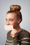 拿着白色卡片的女孩在前边她的嘴唇  图库摄影