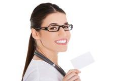 拿着白色卡片的女性医生画象 图库摄影