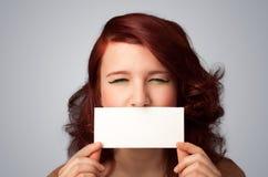 拿着白色卡片的逗人喜爱的女孩在前边她的有拷贝spac的嘴唇 免版税图库摄影