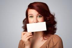 拿着白色卡片的逗人喜爱的女孩在前边她的有拷贝spac的嘴唇 库存图片