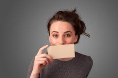 拿着白色卡片的逗人喜爱的女孩在前边她的有拷贝spac的嘴唇  免版税库存照片