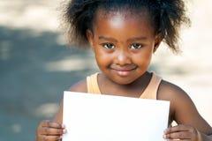 拿着白色卡片的非洲女孩 免版税图库摄影