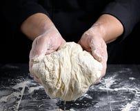 拿着白色发酵面团的球人的手 免版税库存照片