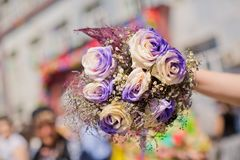拿着白色和紫色花花束 免版税库存图片