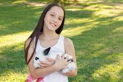 拿着白色和黑小兔子的逗人喜爱的微笑的青少年的女孩 库存照片