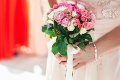 拿着白色和biege玫瑰的婚礼花束礼服的妇女 库存图片