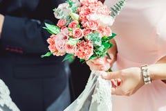 拿着白色和biege玫瑰的婚礼花束礼服的妇女 免版税库存图片