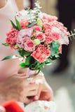 拿着白色和biege玫瑰的婚礼花束礼服的妇女 库存照片