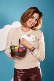 拿着白色小的复活节兔子的美丽的妇女取暖鸡蛋 免版税库存图片