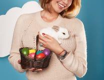 拿着白色小的复活节兔子的美丽的妇女取暖鸡蛋 图库摄影