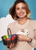 拿着白色小的复活节兔子的美丽的妇女取暖鸡蛋 免版税库存照片