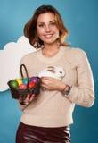 拿着白色小的复活节兔子的美丽的妇女取暖鸡蛋 免版税图库摄影